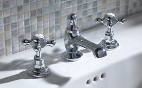 A white basin with 3 hole filler taps attache. tHE TAPS ARE IN cHROME.
